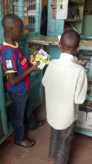 Josphat and john choosing story books at the bookshop