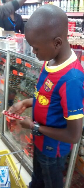 josphat picking some pencils at the supermarket