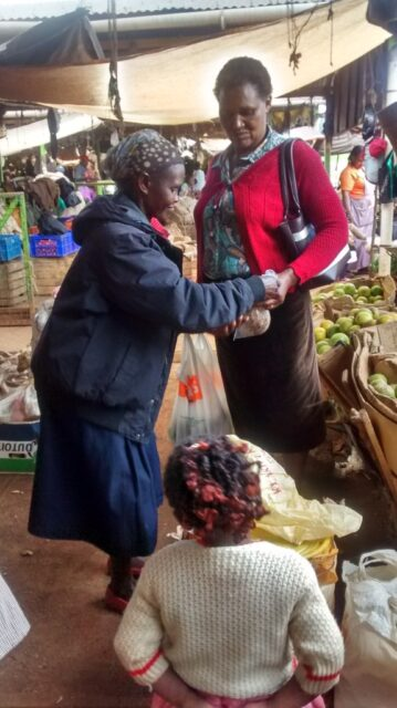 Joephine at the market serving a customer