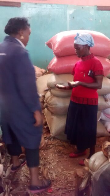 Josephine at the market buying the maize and beans for cooking