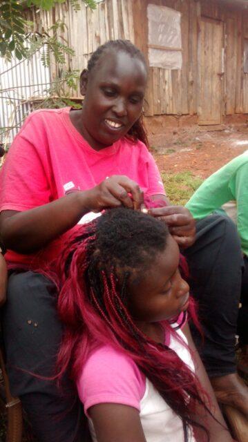 wandia plaiting a customer's hair