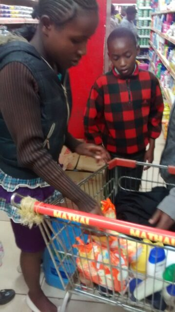 The kids putting some school shopping in the trolley