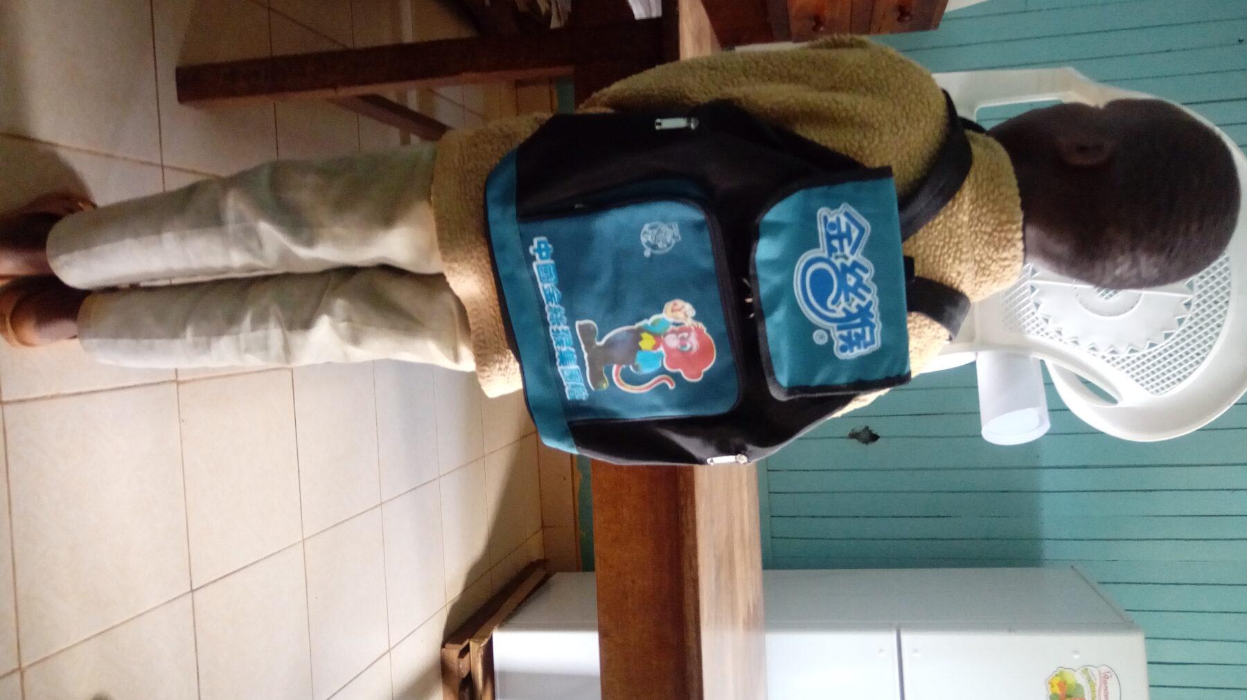 Njiraini carrying his bag