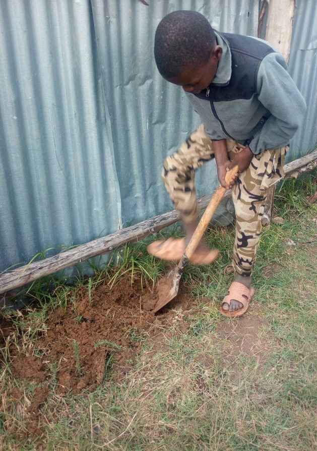 Kinoti (YOU.REP Kid) making a whole for planting the tree
