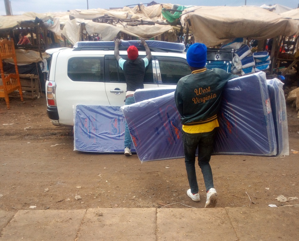 The shop attendants loading the mattress on the car